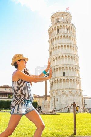 Divertida joven mujer apoyando torre inclinada de pisa, toscana, ita