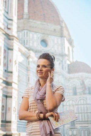 Photo pour Joyeux jeune femme avec carte et audioguide devant la cattedrale di santa maria del fiore à florence, Italie - image libre de droit