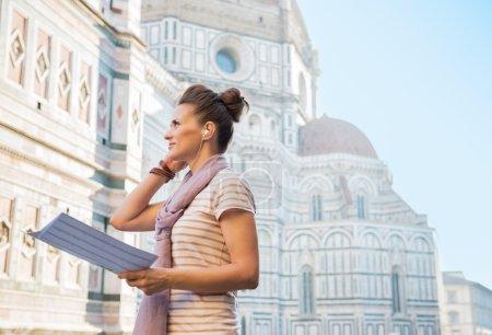 Photo pour Jeune femme avec carte et audioguide debout devant la cattedrale di santa maria del fiore à florence, Italie - image libre de droit