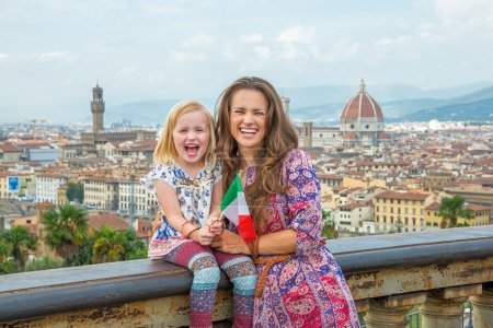 Happy mother and baby girl with flag against panoramic view of florence, italy
