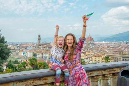 Happy mother and baby girl with flag rejoicing against panoramic view of florence, italy