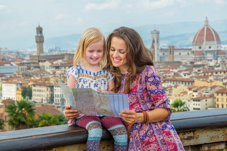 Happy mother and baby girl looking at map against panoramic view of florence, italy