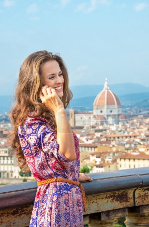 Happy young woman talking cell phone against panoramic view of f