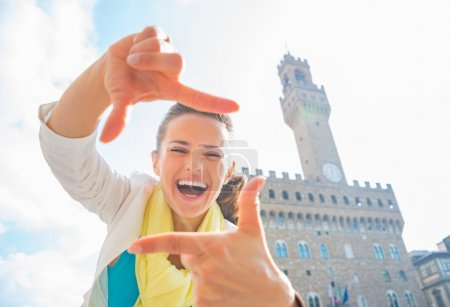 Happy young woman framing with hands in front of palazzo vecchio