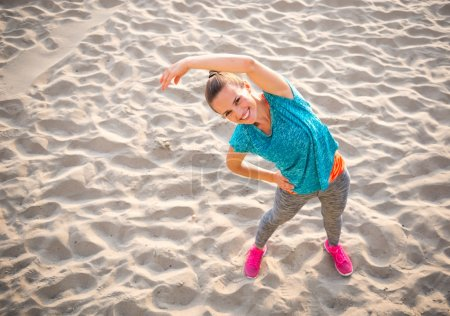 Fitness young woman stretching on beach