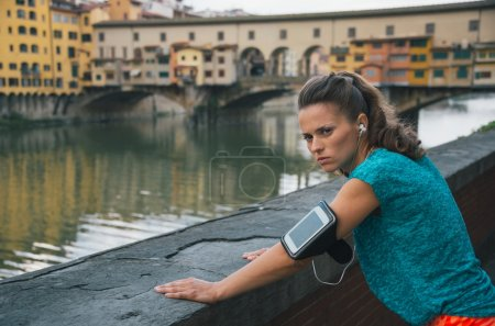 Serious fitness woman standing in front of ponte vecchio in flor