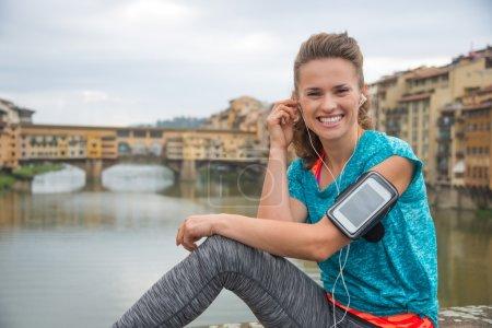 Portrait of happy fitness woman in earphones in front of ponte v