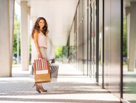 Brown-haired woman smiling holding colourful shopping bags