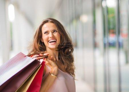 Photo pour Une femme brune maintenant trois sacs à provisions - brun, or et rouge - au dessus de son épaule droite revient à quelqu'un qui lui fait rire. Une bonne séance de magasinage rend n'importe quelle femme heureuse. Elle se contente, respire l'élégance et le style sans effort. Elle lo - image libre de droit