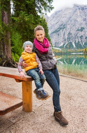 Photo for A mother leans on the wooden picnic table her daughter is sitting on. They are resting. Dressed in outdoor gear and hiking boots, they are smiling. The lake in the background perfectly mirrors the Dolomites and the autumn colours. - Royalty Free Image