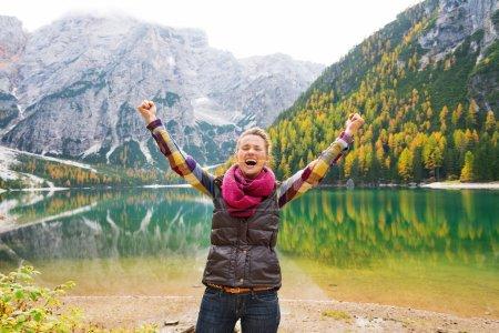Photo pour Une randonneuse heureuse et souriante applaudit de joie sur les rives du lac Bries. En arrière-plan, l'eau calme reflète les couleurs automnales dans les arbres et les montagnes de Dolomite. Le grand air . - image libre de droit