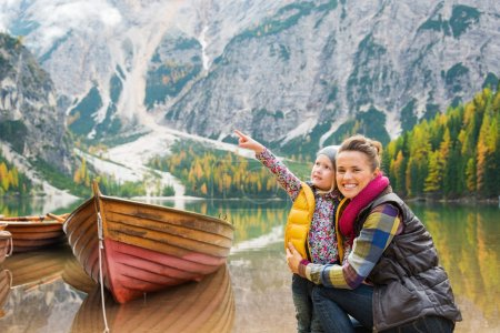 Photo pour A smiling brunette mother kneels next to her daughter, hugging her. The daughter is looking at, and pointing up to the scenery. In the background, wooden boats float on still water. Autumn colours, the Dolomite mountains, and forest create ideal hiki - image libre de droit