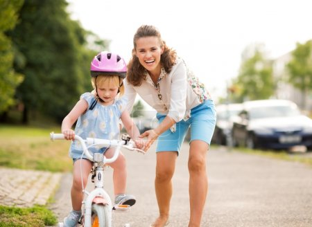 Happy mother pushes daughter on her bike as she learns to ride