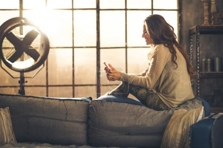 Profile shot of woman sitting on sofa back texting on phone