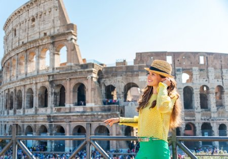 Photo pour Écouter un peu d'opéra pendant qu'elle visite Rome... Quelle ville magique Rome est. Un touriste heureux se tient debout réajustant ses écouteurs alors qu'elle sourit au loin, écoutant de la musique près du Colisée de Rome . - image libre de droit