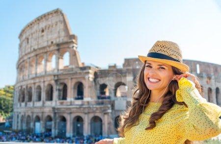 Photo pour Rien de tel que d'écouter quelques morceaux tout en étant un touriste. Une femme heureuse et souriante se tient près du Colisée, réajustant ses écouteurs . - image libre de droit