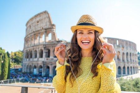 Photo pour Une femme heureuse et souriante se tient près du Colisée, enlève ses écouteurs . - image libre de droit