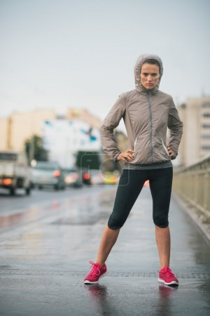 Woman runner wearing rain gear feeling determined