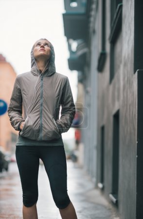 Athletic woman with hands in pockets looking up at gray sky