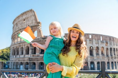 Smiling mother holding daughter with Italian flag and Colosseum