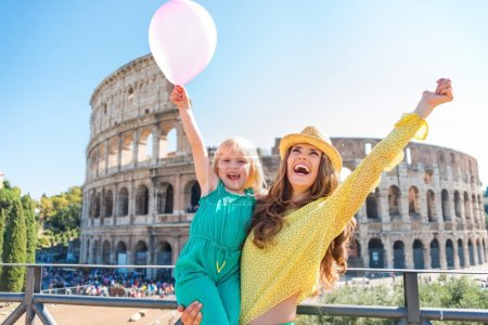 Cheering mother and daughter with pink balloon at Colosseum