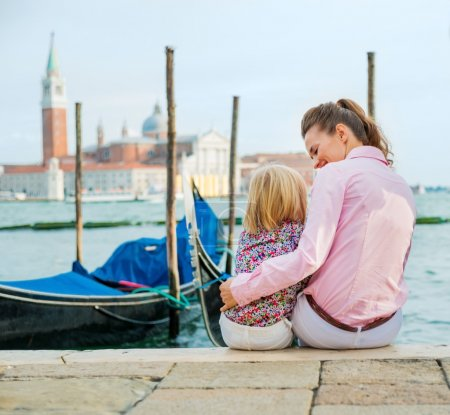 Mother and daughter sitting near gondolas in Venice