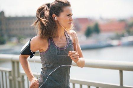 Jogging woman on bridge listening to music