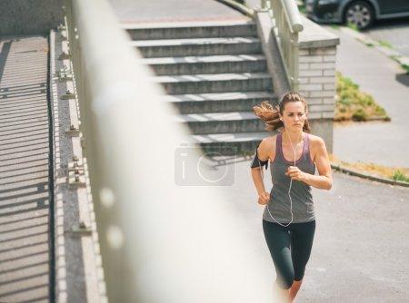 Photo pour Une étape à la fois, et l'objectif est atteint. Une femme joggeuse se concentre sur la voie à suivre, concentrée sur la réalisation de son objectif . - image libre de droit
