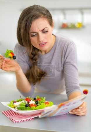 Photo for Young woman eating greek salad in kitchen and reading magazine - Royalty Free Image