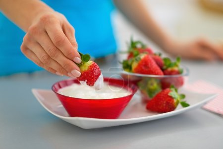 Photo for Closeup on happy young woman eating strawberry with yogurt in kitchen - Royalty Free Image