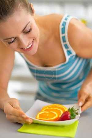 Young woman making fruits plate