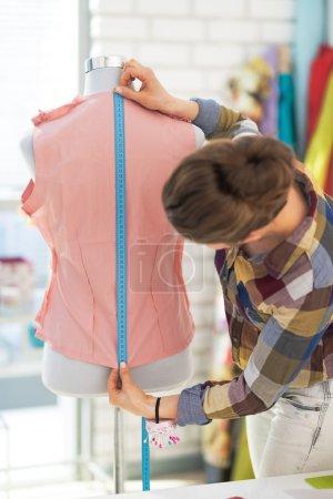 Photo pour Tailleur femme travaillant avec robe en studio. vue arrière - image libre de droit