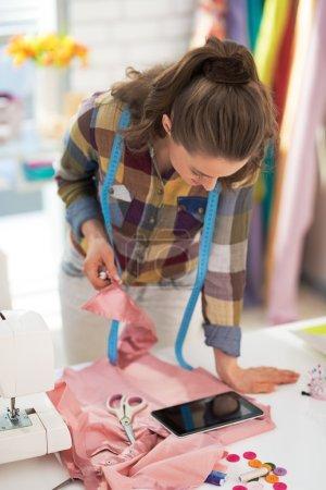 Photo pour Tailleur femme utilisant comprimé pc au travail - image libre de droit