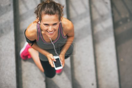 Portrait of smiling fitness young woman with cell phone outdoors