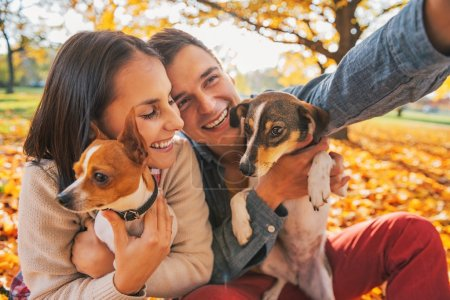 Smiling young couple with dogs outdoors in autumn park making se