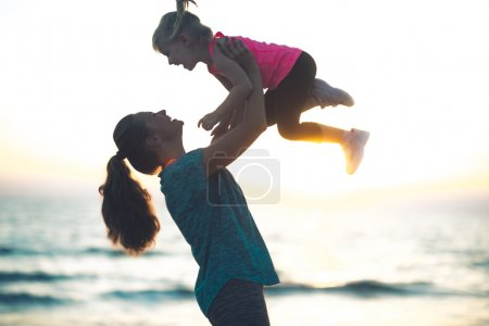 Young mother throwing child up in her air at sunset on the beach