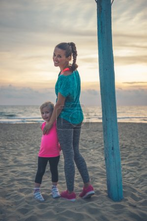 A happy young mother on the beach is standing with her daughter