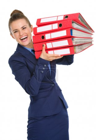 Smiling woman holding stack of files up in the air and laughing