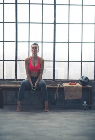 Fit woman sitting on bench in loft gym listening to music