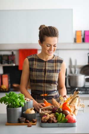 Happy woman in kitchen looking down at autumn vegetables