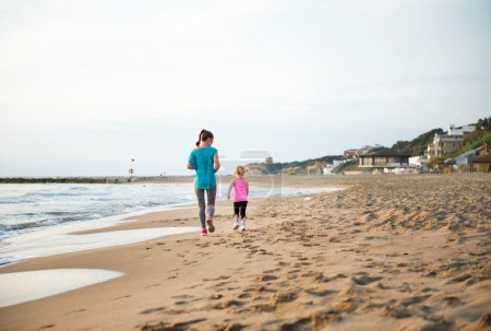 Seen from behind, mother and daughter running on the beach