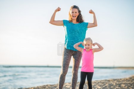 Joyful mother and daughter in fitness gear on beach flexing arms