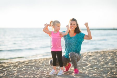 Young mother and daughter in fitness gear on beach flexing arms