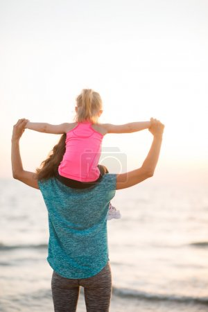 Mother holding young daughter on shoulders at sunset on beach