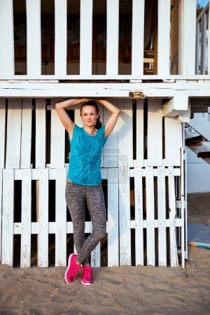 Fit woman standing in workout gear at a beach house