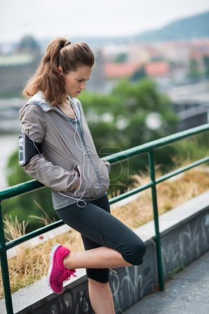 Woman runner with hands in pockets leaning against guardrail