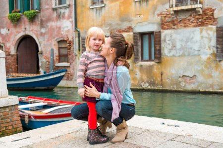 Mother and daughter hugging and cuddling near canal in Venice