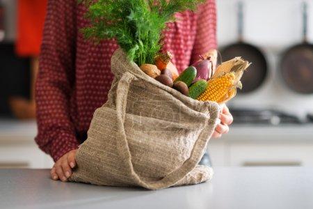 Photo pour Un sac en toile de jute regorge d'une sélection de légumes d'automne, dont le maïs, les concombres, les oignons et les carottes. Les possibilités sont infinies ... - image libre de droit