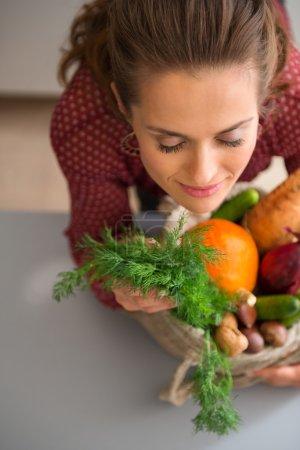 Photo pour L'arôme enivrant des légumes frais. Il n'y a rien de tel. Une femme ferme les yeux avec plaisir, sentant l'odeur délicate et terreuse des légumes d'automne qu'elle a achetés au marché . - image libre de droit