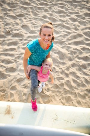 Happy young mother and daughter in fitness gear on the beach